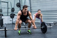 Muscular couple lifting weight together stock photo