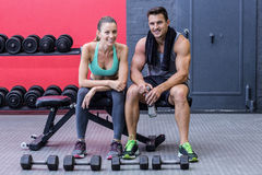 Muscular couple sitting on a bench Royalty Free Stock Images