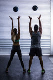 Muscular couple throwing ball in the air Stock Images