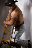 Muscular cowboy leaning on chair Royalty Free Stock Images