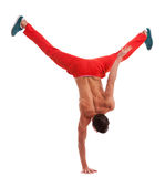 Muscular dancer standing on one hand Stock Images