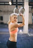 Muscular female athlete exercising with gymnast rings Royalty Free Stock Photos