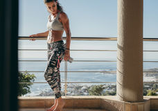 Muscular female in balcony with water bottle Stock Images