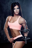 Muscular female body. Young strong athlete posing on dark textured background Royalty Free Stock Photography