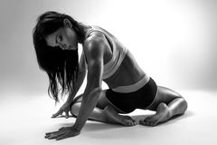 Muscular female body. Young strong athlete posing on grey background. Black-and-white contrast photo stock images