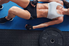 Muscular female on exercise mat with weight plate. Top view cropped shot of muscular female lying on exercise mat with a heavy weight plate on floor Royalty Free Stock Images