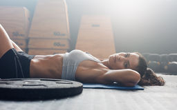 Muscular female relaxing after exercise session. Shot of fitness woman lying on floor with her hands behind head and looking at camera. Muscular female relaxing Royalty Free Stock Photography