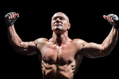 Muscular fighter with arms raised Stock Photo