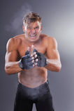 Muscular Fighter Claps with Dusty Gloves for Fight and Motivate Himself Royalty Free Stock Photos