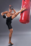 Muscular Fighter Practicing Some Kicks with Punching Bag. In Black Boxing Gloves. Boxing on Gray Background. The Concept of a Healthy Lifestyle Stock Image
