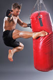 Muscular Fighter Practicing Some Kicks with Punching Bag. Stock Photos