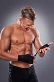 Muscular Fighter Prepare Gloves for Fight and Motivate Himself. Royalty Free Stock Photos