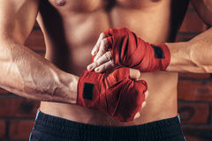 Muscular Fighter With Red Bandages against the background of a brick wall Stock Photography