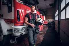 Muscular fireman holding a protective helmet in a garage of a fire department. Leaning on a fire engine and looking outside stock images
