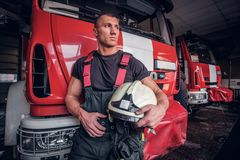 Muscular fireman holding a protective helmet in a garage of a fire department. Leaning on a fire engine and looking outside royalty free stock photos