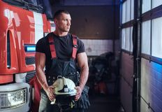 Muscular fireman holding a protective helmet in a garage of a fire department. Standing next to a fire engine and looking outside royalty free stock photography