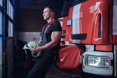 Muscular fireman holding a protective helmet in a garage of a fire department. Leaning on a fire engine and looking outside stock photos