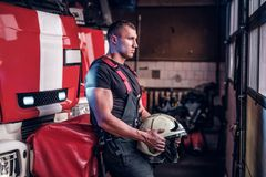 Muscular fireman holding a protective helmet in a garage of a fire department. Leaning on a fire engine and looking outside stock photo