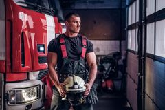 Muscular fireman holding a protective helmet in a garage of a fire department. Standing next to a fire engine and looking outside stock images