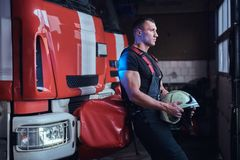 Muscular fireman holding a protective helmet in a garage of a fire department. Leaning on a fire engine and looking outside royalty free stock image