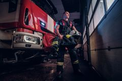 Muscular fireman holding a protective helmet in a garage of a fire department. Standing next to a fire engine and looking outside stock photography