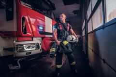 Muscular fireman holding a protective helmet in a garage of a fire department. Standing next to a fire engine and looking sideways stock image