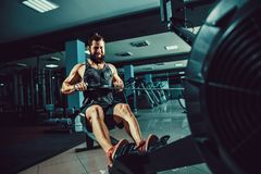 Muscular fit man using rowing machine at gym Stock Photo