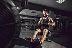 Muscular fit man using rowing machine at gym. Bearded Muscular Fit Man Ssing Rowing Machine at Functional Training Gym Stock Photography