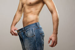 Muscular fit man wearing big jeans after diet. Closeup studio shot of a young Caucasian fit man wearing big jeans after diet. Copy space available. Diet, healthy royalty free stock images