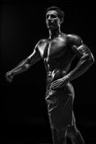 Muscular and fit young bodybuilder fitness male model posing ove Stock Photos