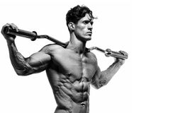 Muscular and fit young bodybuilder posing demonstrates the core. Muscles. Isolated on white background Stock Images