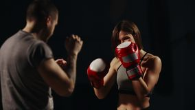 Muscular fitness girl training with his instructor to carry out strikes on the feet in Boxing gloves. The lesson of self. Defense. A Boxing workout stock video