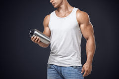 Muscular fitness male holding protein shake bottle Royalty Free Stock Photo