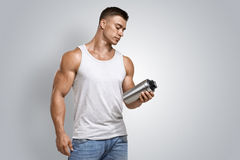Muscular fitness male holding protein shake bottle. Muscular fitness male bodybuilder holding protein shake bottle ready for drinking. Studio shot on white Royalty Free Stock Photos