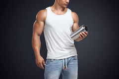 Muscular fitness male model holding protein shake bottle royalty free stock photos