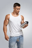 Muscular fitness male model holding protein shake bottle stock images
