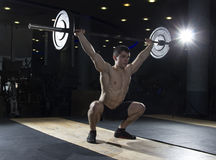 Muscular fitness man deadlifts a barbell over his head in the gy Royalty Free Stock Images