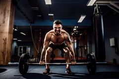 Muscular fitness man doing deadlift a barbell in modern fitness center. Functional training. Muscular strong fitness man doing deadlift of a barbell in modern Royalty Free Stock Photography