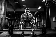 Muscular fitness man doing deadlift a barbell over his head in modern fitness center. Functional training. Snatch exercise Royalty Free Stock Photo