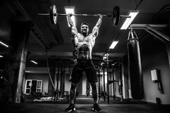 Muscular fitness man doing deadlift a barbell over his head in modern fitness center. Functional training. Snatch exercise Stock Photos