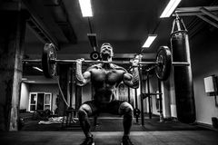 Muscular fitness man doing deadlift a barbell over his head in modern fitness center. Functional training. Snatch exercise Stock Image