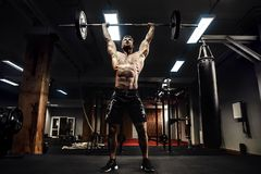 Muscular fitness man doing deadlift a barbell over his head in modern fitness center. Functional training. Snatch exercise Royalty Free Stock Photos