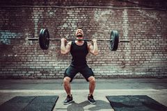Muscular fitness man doing deadlift a barbell over his head in outdoor, street gym. Functional training.