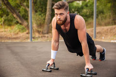 Muscular fitness man doing push-ups and using sports equipment. Outdoors Royalty Free Stock Images