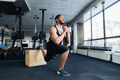 Muscular fitness man doing squats in the gym Stock Photos