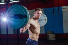 Muscular fitness man preparing to deadlift a barbell over his head in modern fitness center.Functional training.Snatch. Exercise Royalty Free Stock Image