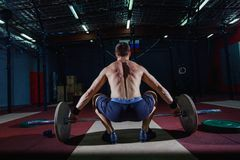 Muscular fitness man preparing to deadlift a barbell over his head in modern fitness center.Functional training.Snatch. Exercise Royalty Free Stock Photos
