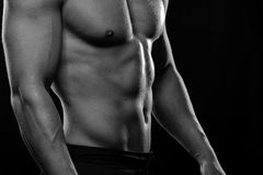 Muscular fitness model posing shirtless. Muscular fitness model with body posing shirtless. Fit man posing on black background, showing abdominal muscles. Sports stock photos