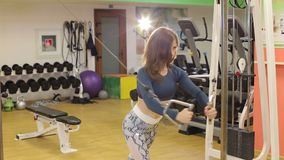 Muscular fitness woman trains triceps. Girl exercise with Cable Crossover in gym