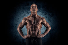Muscular guy on black background Stock Photos